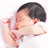 Newborn baby sleeping in bed.