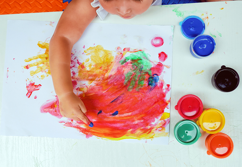 Young child finger-painting with colored paint on a poster in a learning center.
